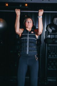 woman in weight vest doing pullup